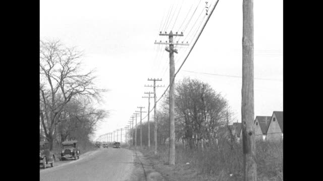 telephone lines on row of telephone poles along road cars on road / note exact year not known documentation incomplete - privatfahrzeug stock-videos und b-roll-filmmaterial