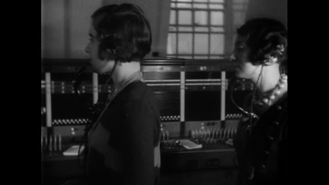 montage telephone operators sitting before switchboards at a telephone exchange / london, england, united kingdom - 1933 stock videos & royalty-free footage