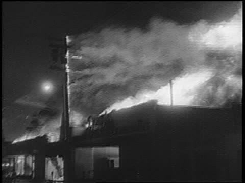 B/W 1965 telephone pole building on fire at night in Watts race riots / Los Angeles / newsreel
