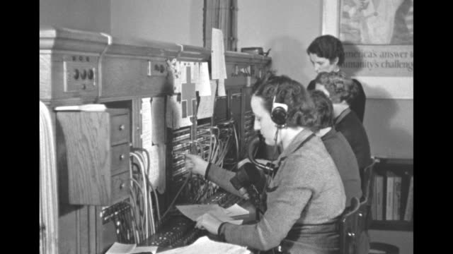 telephone switchboard operators and a closeup of a woman's hand plugging cords into the board a woman speaking into a chest microphone / note exact... - 電話交換機点の映像素材/bロール