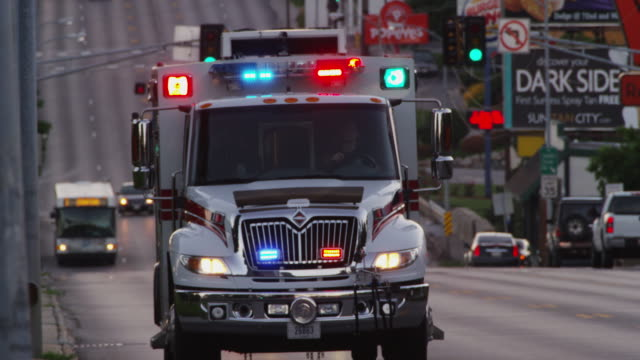 telephoto lens of an emergency ambulance with lights flashing, driving down a metro urban city street at twilight. - televisione a ultra alta definizione video stock e b–roll