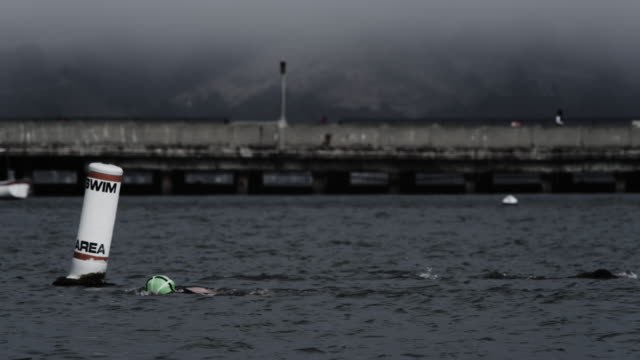 telephoto lens, senior woman swims in san francisco bay, bases buoy and other swimmers. - san francisco bay stock videos & royalty-free footage
