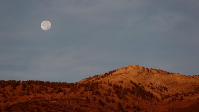 telephoto shot full moon rising over golden light covered mountain at sunrise. - gebirgskamm stock-videos und b-roll-filmmaterial