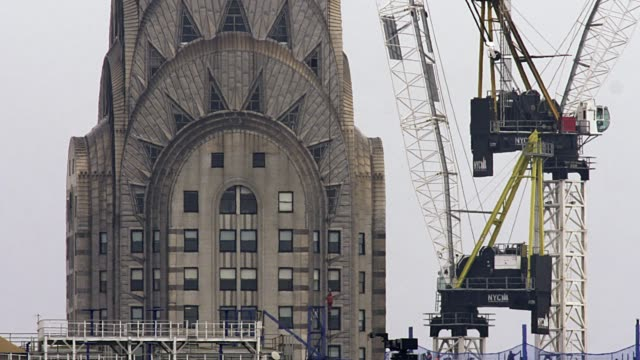 a telephoto shot of a crane working in front of the chryster building. - chrysler building stock-videos und b-roll-filmmaterial