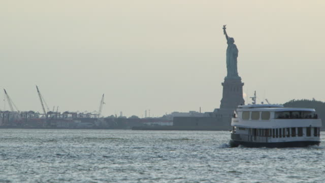 telephoto shot of a ferry passing the statue of liberty on the hudson river. - new york harbor stock videos & royalty-free footage