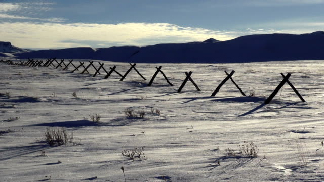 vidéos et rushes de telephoto shot of barbed wire fence on snowdrift covered landscape. - neige fraîche
