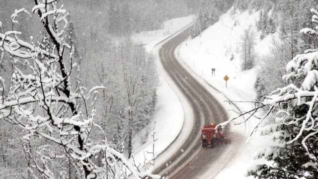 Telephoto shot of paved road highway being plowed by snowplow in winter during heavy puffy snowfall snow storm.