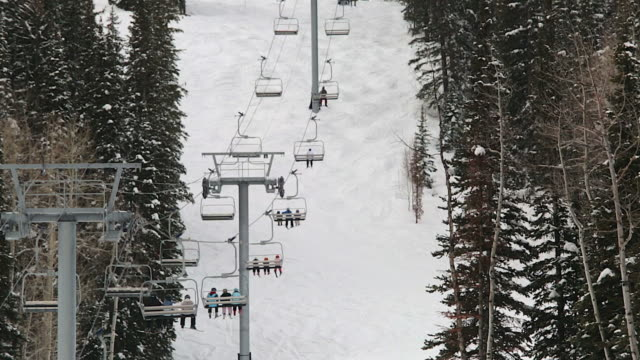 Telephoto shot of people riding on a ski lift at a mountain near salt lake city, utah
