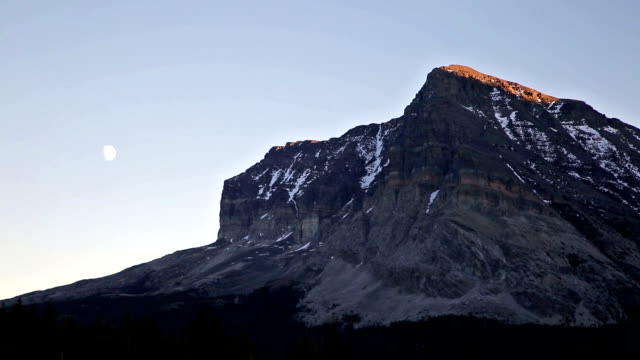 Telephoto shot of snow covered mountain peak at sunset with 3/4 moon