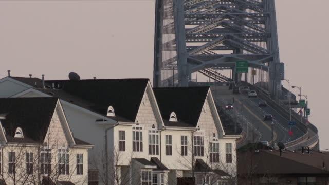 vídeos de stock, filmes e b-roll de a telephoto shot of the bayonne bridge and a row of townhomes in front. - nova jersey