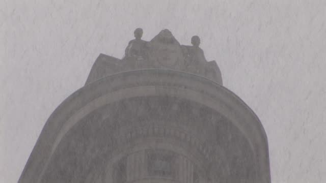 Telephoto shot of the Flatiron Building exterior/lady waiting to cross the street as the very heavy snow falls/skyward shots of the snow...