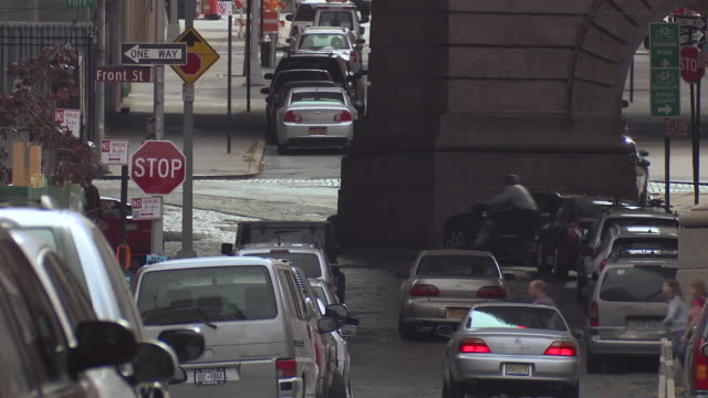 a telephoto shot of underneath the manhattan bridge in brooklyn bridge, cars are parked on the sides of the road. - bicycle parking station stock videos and b-roll footage