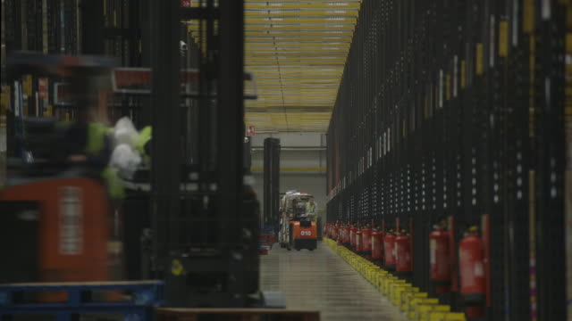 Telephoto view of a long central corridor at a busy food distribution warehouse, UK.
