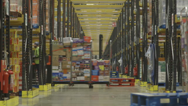Telephoto view of a long central corridor in a busy food distribution warehouse in the UK.