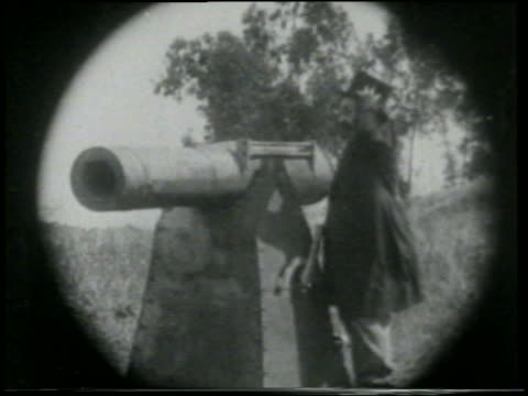 stockvideo's en b-roll-footage met b/w 1915 telescope point of view man (chester conklin) on grassy hill preparing to fire cannon / short - 1915