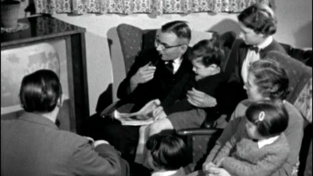 people still have black and white tv licences; family gathered around tv set - bericht film und fernsehen stock-videos und b-roll-filmmaterial