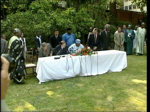 London Nigerian President Olusegun Obasanjo and others sitting at table set out in garden for press conference Obasanjo speaking into microphone