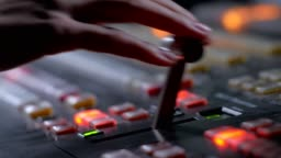 television director is moving handle on a control panel during tv filming in studio