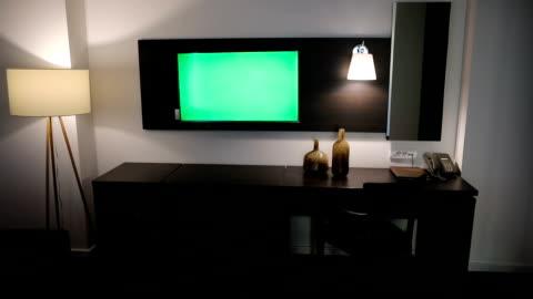 vídeos y material grabado en eventos de stock de verde del televisor en la habitación del hotel - pantalla de cristal líquido