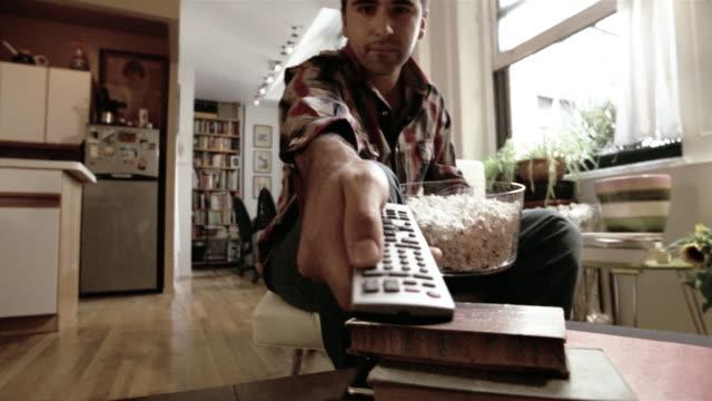 MS Television POV of man eating popcorn + using remote control/ New York City