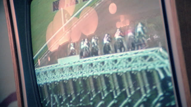 a television screen shows horses breaking from the starting gate and galloping over the track. - horse racing stock videos & royalty-free footage