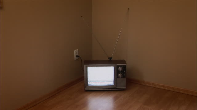 television set sitting in corner of room on the floor / plugged into outlet and showing static - television static stock videos & royalty-free footage