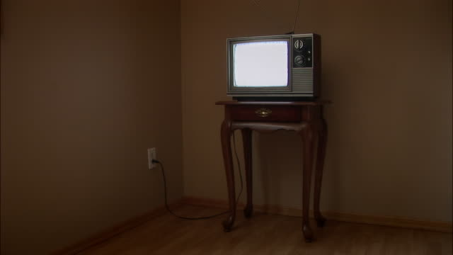 Television set sitting on end table corner of room on the floor / plugged into outlet and showing static