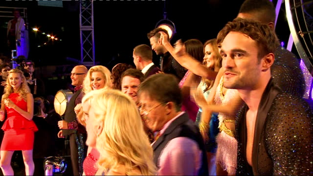 strictly come dancing 2014 launch: launch and interviews; group posing for family photograph / gibney having makeup retouched / celebrities dancing... - クラウディア ウィンクルマン点の映像素材/bロール
