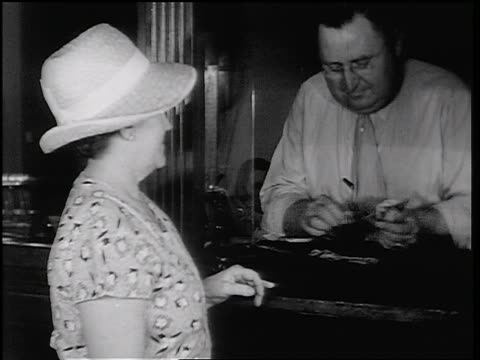 b/w 1934 teller counting money + handing it to woman in fon du lac bank / east peoria, il / newsreel - us dollar note stock videos & royalty-free footage