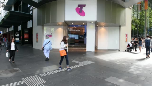 a telstra telephone booth sits on the pavement in bourke street mall in melbourne australia on tuesday feb 2016 the telstra logo is displayed on top... - public phone stock videos & royalty-free footage