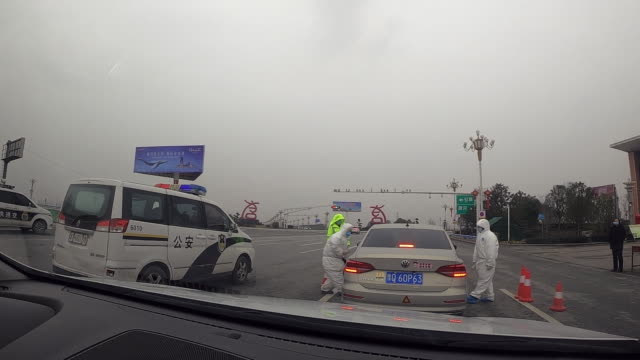 temperature scans being administered at a checkpoint to hubei province in an attempt to prevent the spread of the coronavirus - blocco stradale video stock e b–roll