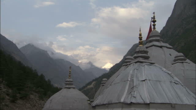 temple domes and mountains, gangotri, india available in hd. - temple building stock videos & royalty-free footage