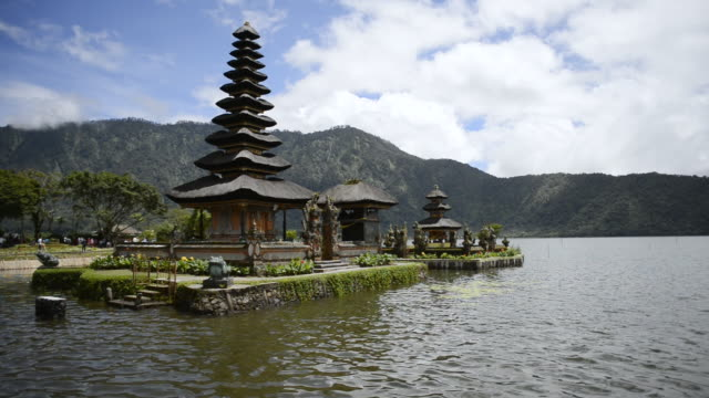 ws temple in lake and mountains in distance with clouds moving over / lake bratan, indonesia - pura ulu danau temple stock videos & royalty-free footage