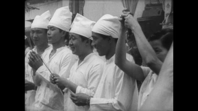vidéos et rushes de ext temple in malaysia / chinese pilgrims dressed all in white in a crowd / pilgrims in a line holding smoking incense sticks / two men rake a giant... - cérémonie