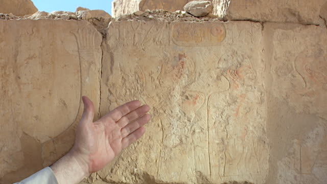 temple of hatshepsut. view of a hand pointing to the painted figure and the fluted decorations on top the prow of a boat. - tempio di hatshepsut video stock e b–roll