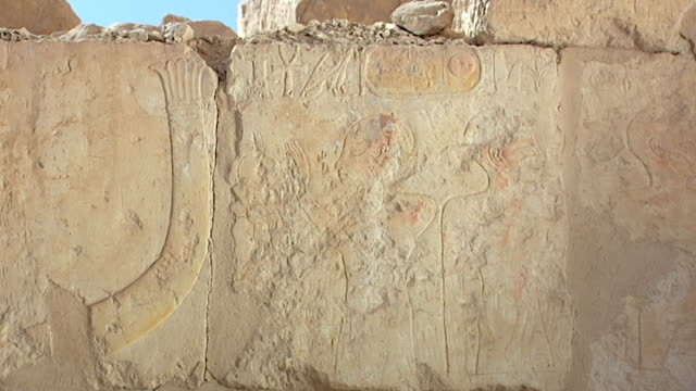 temple of hatshepsut. wide view of a painted figure facing the prow of a boat. - tempio di hatshepsut video stock e b–roll