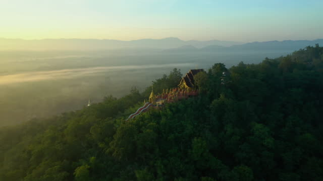 stockvideo's en b-roll-footage met tempel op de berg met mist bij sunrise time luchtfoto en zoom uit schot - tempel
