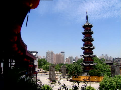 temple pagoda with modern skyline in background shanghai - pagoda stock videos and b-roll footage