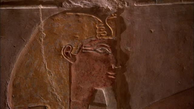 vídeos de stock, filmes e b-roll de a temple wall carving depicts queen hatshepsut wearing her false beard of pharanoic power. available in hd. - templo de hatshepsut
