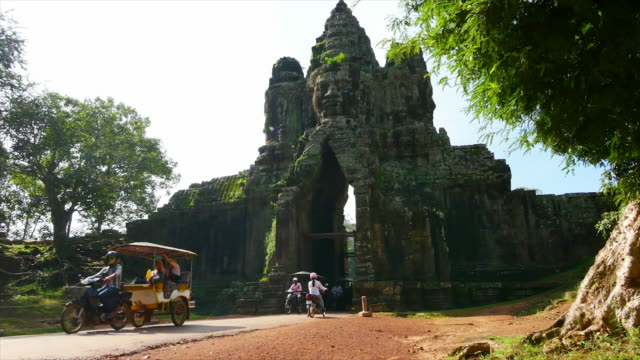 temple with people on motors passing through - angkor wat stock videos and b-roll footage
