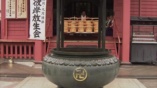 ws temple with priests chanting inside, tokyo, japan - insignier bildbanksvideor och videomaterial från bakom kulisserna