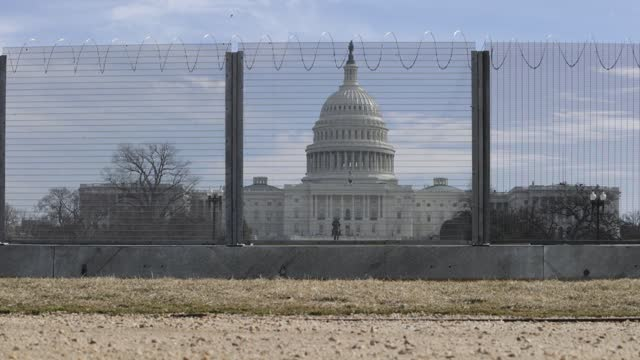 temporary security fence topped with concertina razor wire circles the u.s. capitol on february 17, 2021 in washington, dc. the fence was erected... - demokratie stock-videos und b-roll-filmmaterial