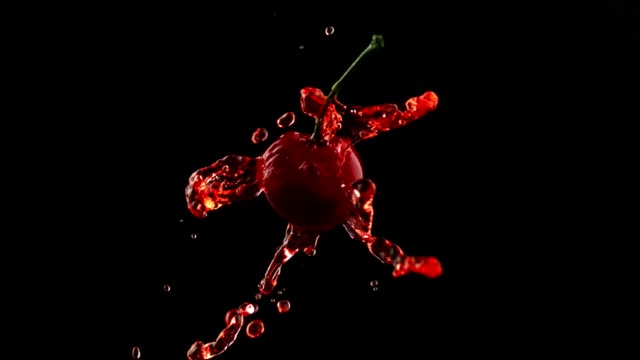 Tempting cherry colliding with cherry juice. Super slow motion