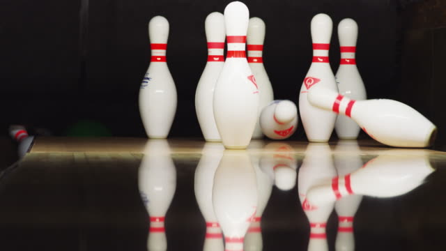 ten bowling pins stand at the end of an alley; a green bowling ball approaches and knocks down six pins. - bowling ball stock videos & royalty-free footage
