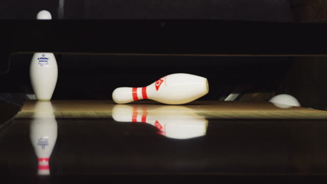 ten bowling pins stand at the end of an alley; a green bowling ball approaches and knocks down nine pins. - elkhorn nebraska stock videos & royalty-free footage