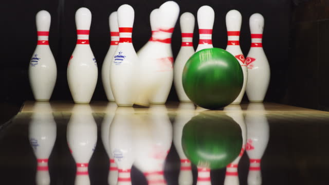 vídeos de stock, filmes e b-roll de ten bowling pins stand at the end of an alley; a green bowling ball approaches and knocks down eight pins leaving a split. - cancha de jogo de boliche
