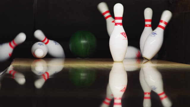 ten bowling pins stand at the end of an alley; a green bowling ball approaches and knocks down eight pins. - eight ball stock videos & royalty-free footage