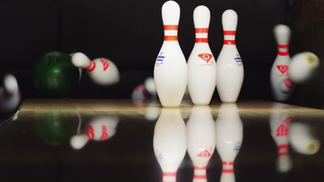 ten bowling pins stand at the end of an alley; a green bowling ball approaches and knocks down seven pins. - elkhorn nebraska stock videos & royalty-free footage
