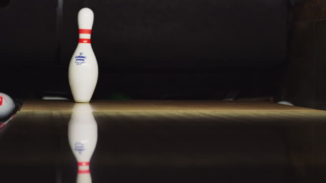 ten bowling pins stand at the end of an alley; a green bowling ball approaches and knocks down nine pins; the last pin wobbles, almost a strike. - elkhorn nebraska stock videos & royalty-free footage