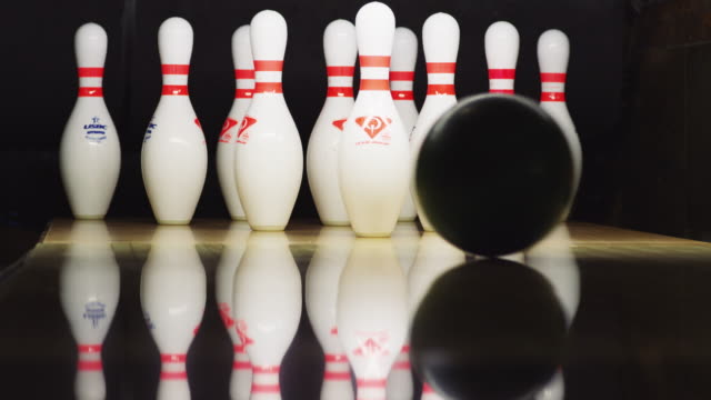 vídeos de stock, filmes e b-roll de ten bowling pins stand at the end of an alley; a green bowling ball approaches and knocks down ten pins; a strike! - cancha de jogo de boliche